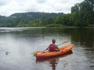 A paddler moves down the gentle Dordogne towards the hill-top village of Domme .